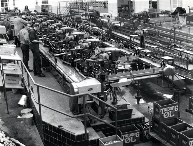 Samlebånd og maskiner tager over. 70 år senere er der ikke mange mennesker tilbage i tappehallen. Maskiner og samlebånd dominerer, mens et par medarbejdere overvåger produktionen. Produktionen var også blevet noget mere effektiv: Nu kunne man fremstille 30.000 øl i timen.